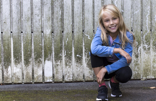 Portrait of smiling blond girl crouching in front of wooden wall - JFEF00925