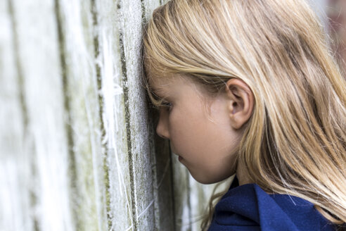 Profile of sad blond girl leaning against wooden wall - JFEF00943