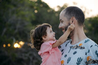 Happy father holding his daughter outdoors at sunset - GEMF02574