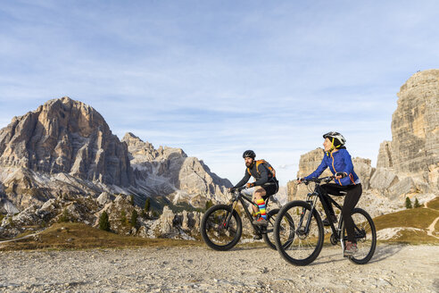 Italy, Cortina d'Ampezzo, two people cycling with mountain bikes in the Dolomites mountains - WPEF01164