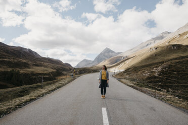 Switzerland, Engadin, woman standing on mountain road - LHPF00147
