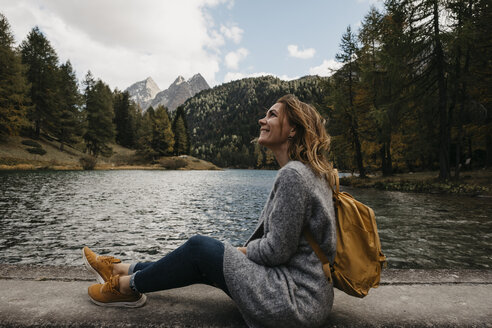 Switzerland, Grisons, Albula Pass, smiling woman on a hiking trip sitting at lakeside in mountainscape - LHPF00153