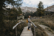 Switzerland, Engadin, woman on a hiking trip on a wooden bridge - LHPF00156