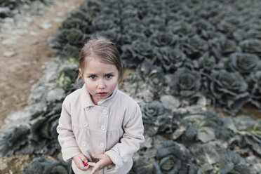 Portrait of a girl standing on a cabbage field - KMKF00663