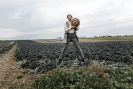 Portrait of a carefree woman jumping on a cabbage field - KMKF00669