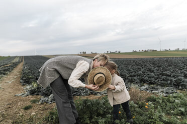 Girl and her mother with straw hat at a cabbage field - KMKF00672