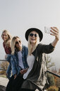 Germany, Black Forest, Sitzenkirch, three happy young women taking a selfie at Sausenburg Castle - LHPF00170