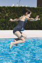 Happy little girl jumping into swimming pool - ERRF00157