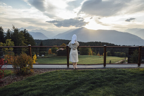Woman waering bathrobe and turban standing at a fence looking at landscape - LHPF00171