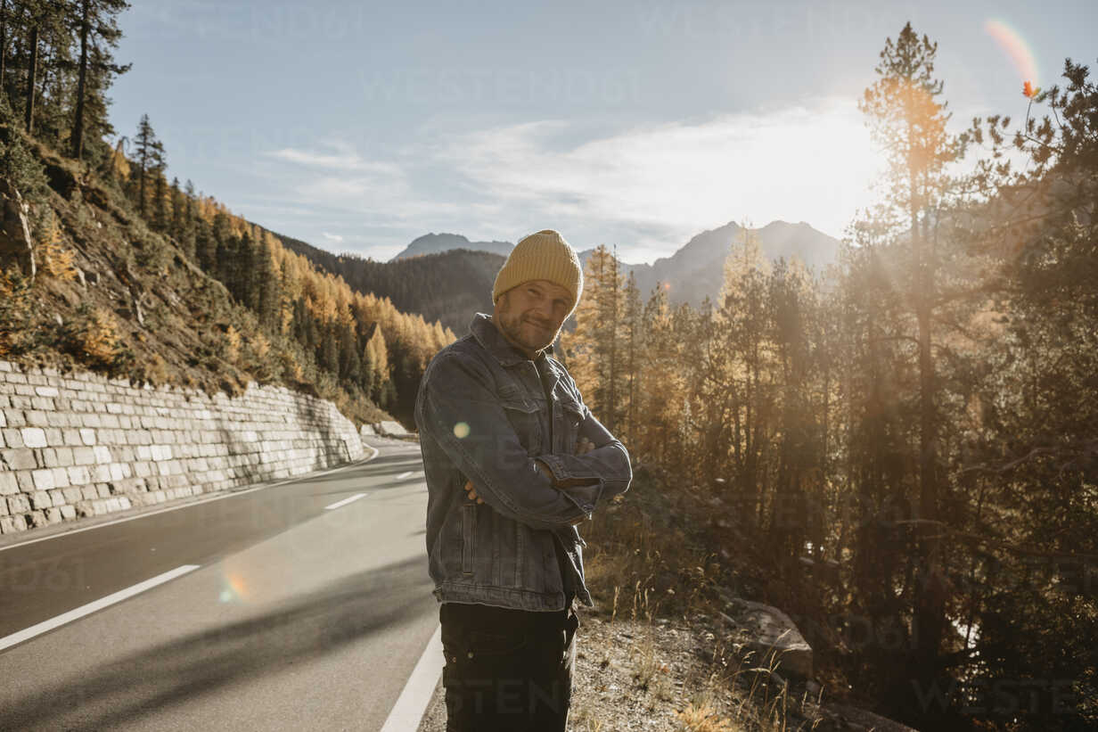 Man travelling through Switzerland, standing on road - LHPF00183 - letizia haessig photography/Westend61