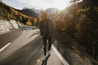 Man travelling through Switzerland, standing on road - LHPF00186