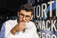 Portrait of young businessman drinking coffee at sidewalk cafe watching something - TCF05971