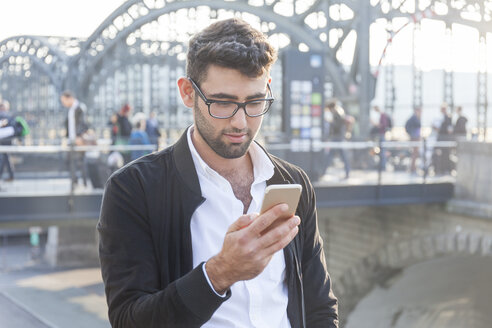 Germany, Munich, young businessman looking at cell phone at central bus station - TCF05974