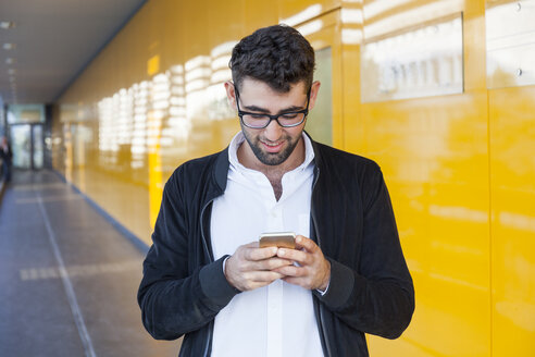 Smiling young businessman using cell phone - TCF05977