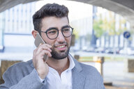 Portrait of smiling young businessman on the phone - TCF05983