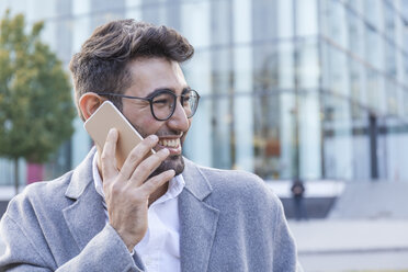 Portrait of laughing young businessman on the phone - TCF05986