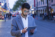Germany, Munich, young businessman using digital tablet in the city at dusk - TCF05998