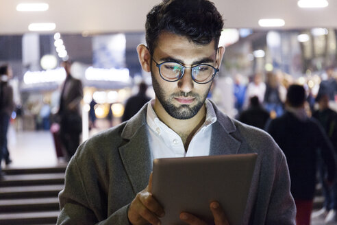 Germany, Munich, portrait of young businessman using digital tablet at central station - TCF06004