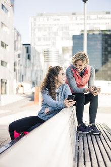 Girlfriends taking a break after training, using smartphone - MOEF01675