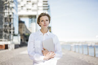 Young woman carrying laptop, portrait - MOEF01702