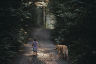Rear view of girl with dog standing on dirt road amidst plants at forest - CAVF56452