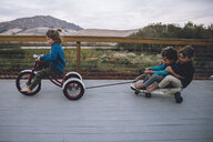 Boy pulling toy car with friends while riding tricycle on floorboard - CAVF56527