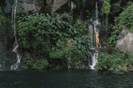 Woman in bikini enjoying waterfall at forest - CAVF56533