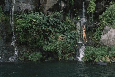 Woman in bikini enjoying waterfall at forest - CAVF56533