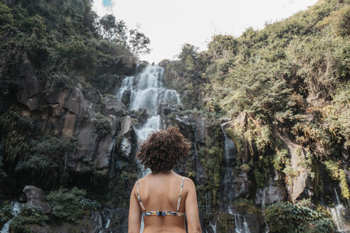 Rear view of woman in bikini standing against waterfall at forest - CAVF56536