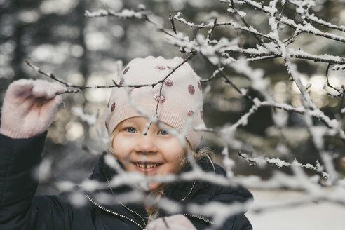 Portrait of cute cheerful girl seen through snow covered dried plants - CAVF56542