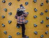 Rear view of boy climbing wall at health club - CAVF56554