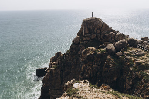 Mid distance view of hiker standing on cliff against sea - CAVF56566