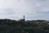 Mid distance view of man standing on rock against cloudy sky - CAVF56569