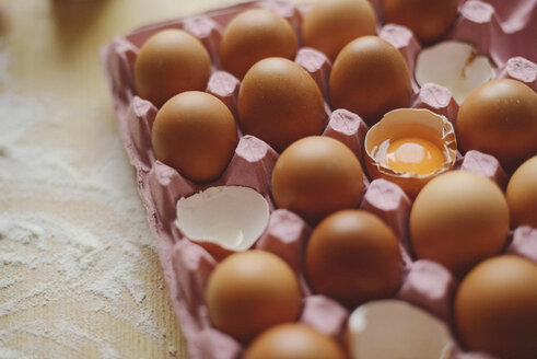 High angle view of eggs in carton on wooden table in kitchen - CAVF56599