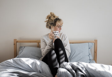 Woman holding coffee cup while sitting on bed at home - CAVF56650