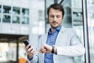 Portrait of a businessman checkin time, using smartphone - DIGF05497