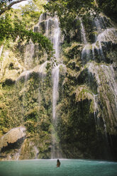Woman swimming in river by waterfall at forest - CAVF56685