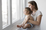 Side view of mother carrying daughter while looking through window at home - CAVF56742