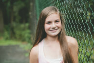 Close-up portrait of confident girl by chainlink fence - CAVF56757