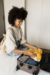 Smiling woman sitting on bed with suitcase - VABF01846