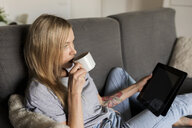 Young woman sitting on couch drinking coffee and holding tablet - VABF01855