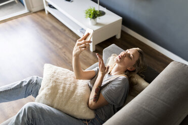 Smiling young woman lying on couch taking a selfie - VABF01861