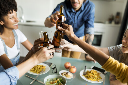 Cheerful friends clinking beer bottles at dining table - VABF01885