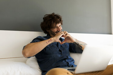 Happy tattooed man with laptop chatting with girlfriend in bed - VABF01936