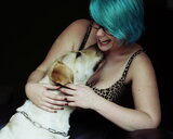 Midsection of a woman with her pet dog on a black background - INGF07926