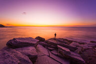 Silhouette man standing on rock at beach against sky during sunset. - INGF08010
