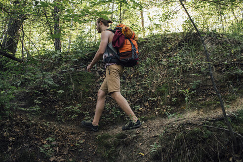 Young man with backpack hiking in a forest - VPIF01164