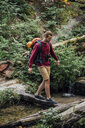 Young hiker with backpack crossing water in the forest - VPIF01176