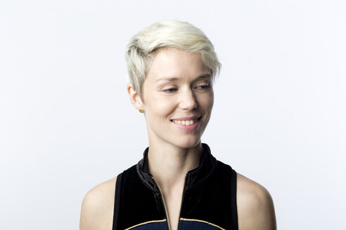 Portrait of smiling woman with short blond dyed hair in front of white background - FLLF00050