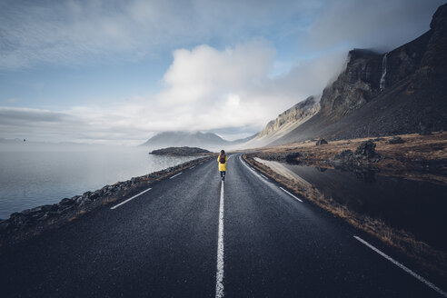 Iceland, back view of woman with backpack walking on median strip of country road - OCMF00121